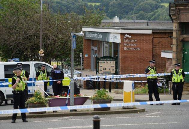 Police stand guard on the perimeter of the crime scene outside the library in Birstall where Jo Cox was