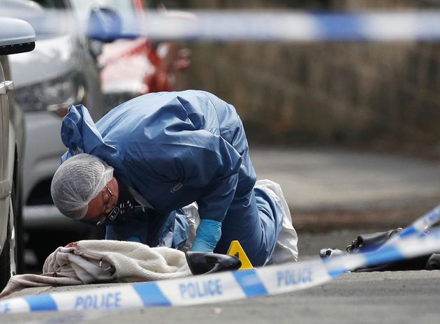 A forensics police officer works next women's shoes and a handbag on the ground behind a police