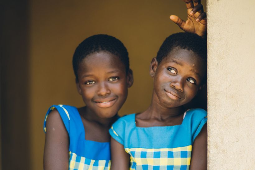 Two young girls take a playful break at the Challenging Heights School, in Ghana.