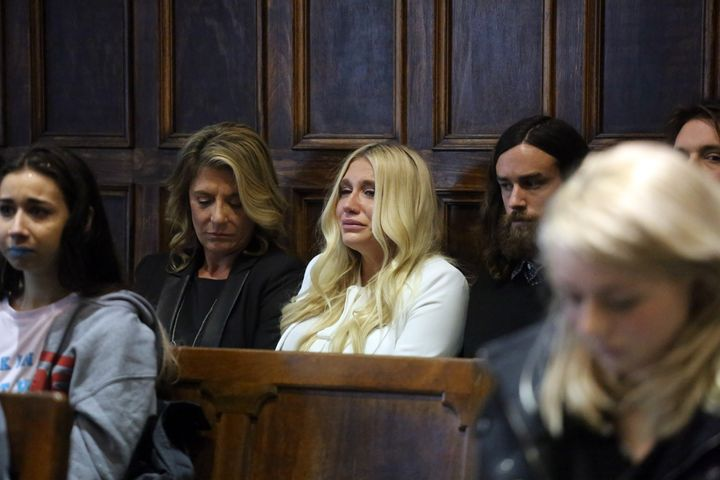Kesha (center in white) cries as she learns she will not be released from her record label contract in Manhattan Supreme Cour
