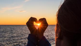 Woman making heart shape at sunset