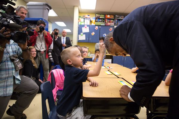 President Barack Obama allows first grader Edwin Caleb to touch his hair during a classroom visit at Clarence Tinker Elementa