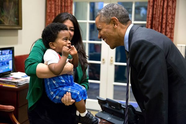 President Barack Obama greets a little boy held by Ferial Govashiri, Personal Aide to the President, in the Outer Oval Office
