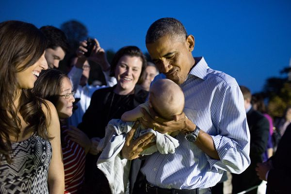 President Barack Obama holds a baby during the Congressional Picnic on the South Lawn of the White House, Sept. 17, 2014. (Of