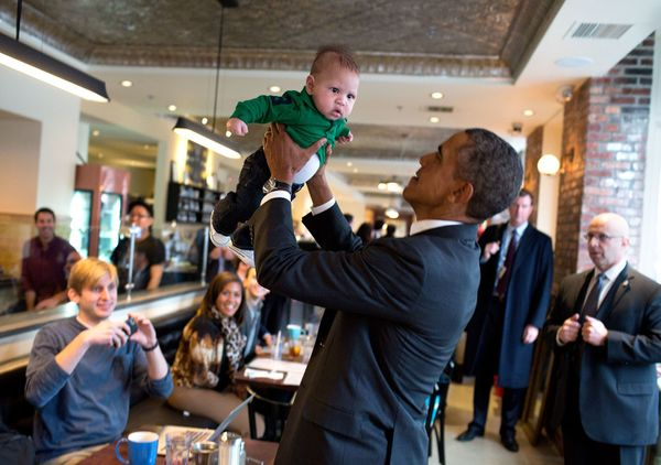 President Barack Obama lifts a baby while greeting patrons prior to lunch at The Coupe restaurant in Washington, D.C., Jan. 1