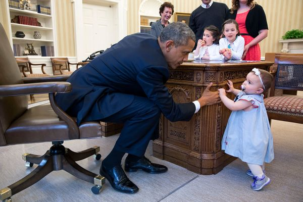 President Barack Obama holds the hand of Lincoln Rose Pierce Smith, the daughter of former Deputy Press Secretary Jamie Smith