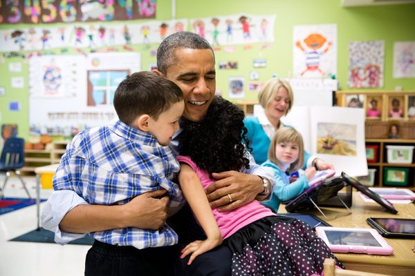 President Barack Obama hugs students during a visit to a pre-kindergarten classroom at the College Heights Early Childhood Le