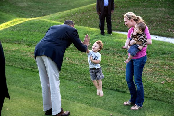 President Barack Obama greets a child on the Kingsmill Resort grounds during a break from debate prep in Williamsburg, Va., O