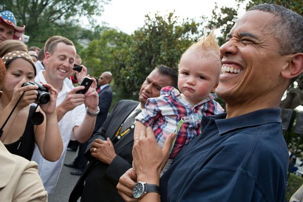 President Barack Obama holds a baby while greeting guests during an Independence Day celebration on the South Lawn of the Whi