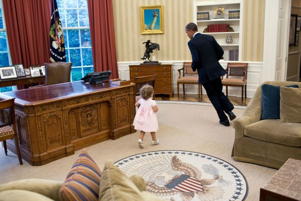 President Barack Obama runs around his desk in the Oval Office with Sarah Froman, daughter of Nancy Goodman and Mike Froman,