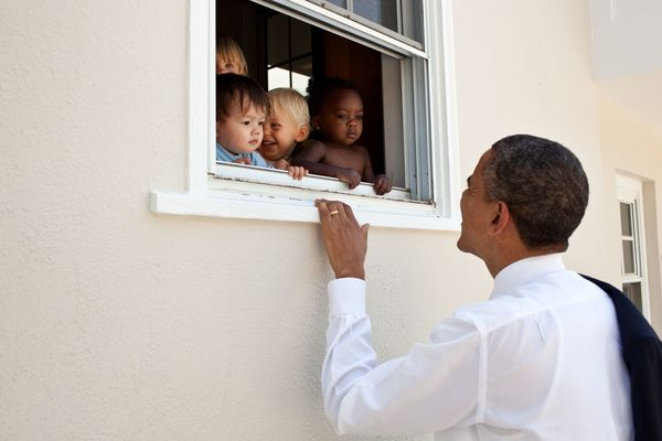 President Barack Obama greets children at a day care facility adjacent to daughter Sasha's school in Bethesda, Md., following