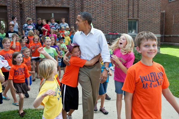 President Barack Obama greets children from the Valleyland Kids summer program outside a school in Chatfield, Minn., during a