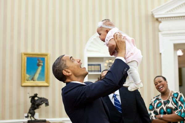 President Barack Obama holds up four-month-old Alia Jawando as her father, William Jawando, Deputy Associate Director of Publ