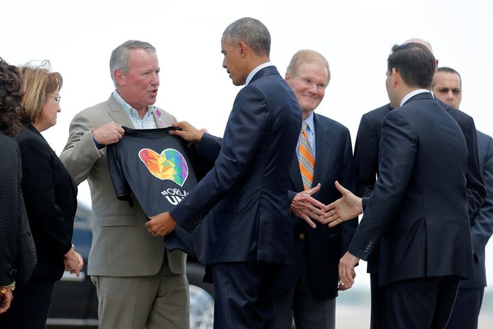 President Barack Obama receives a T-shirt from Orlando Mayor Buddy Dyer as he arrives in the city to meet with families