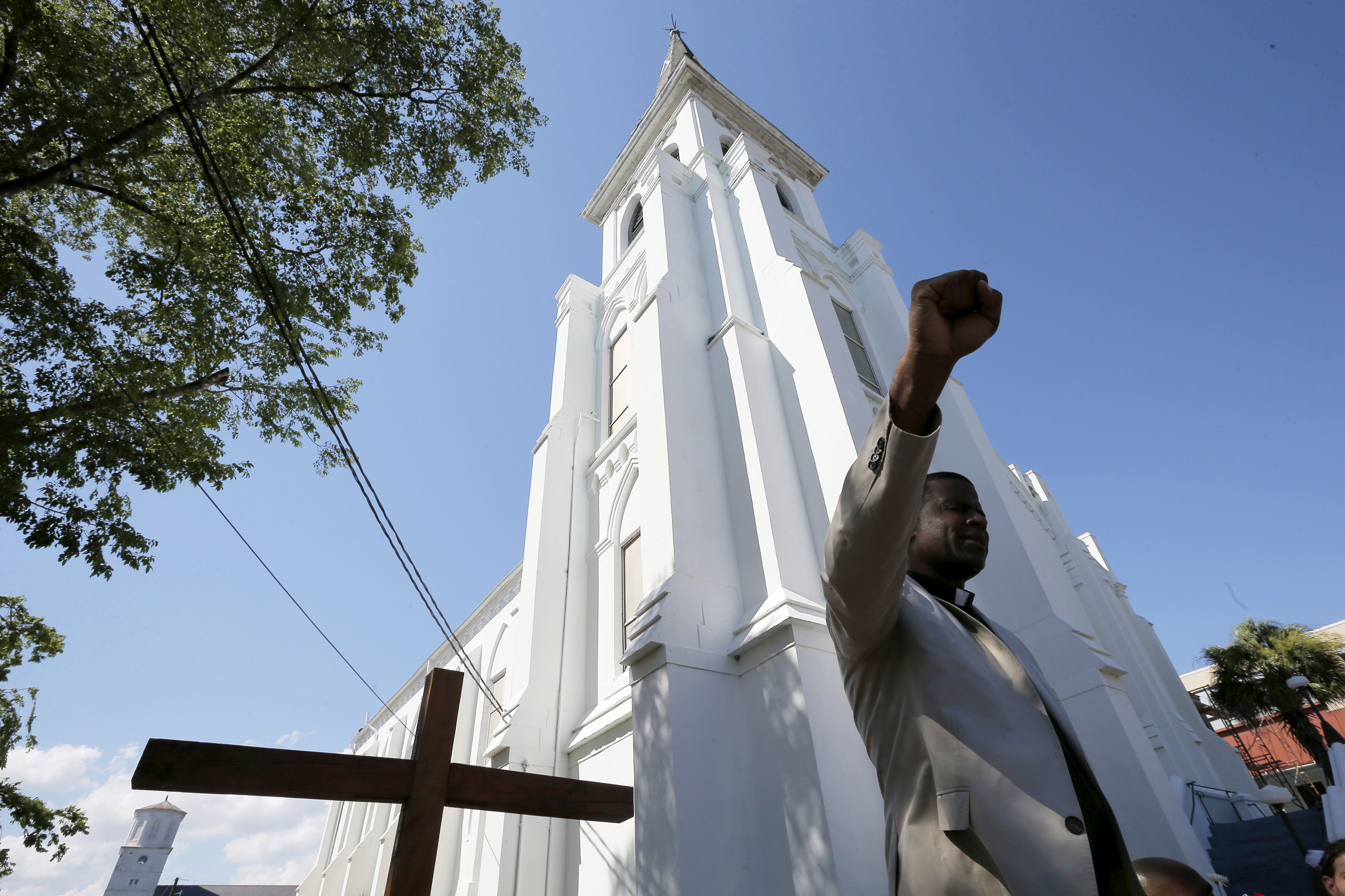 Reverend Dimas Salaberrios leads prayers outside the Emanuel African Methodist Episcopal Church, where a mass shooting took place, in Charleston, South Carolina June 20, 2015. Mourners arrived in Charleston from around the United States on Saturday to pay their respects to nine black churchgoers killed in the attack this week, with services planned throughout the day ahead of a rally in the state capital later in the evening. REUTERS/Brian Snyder