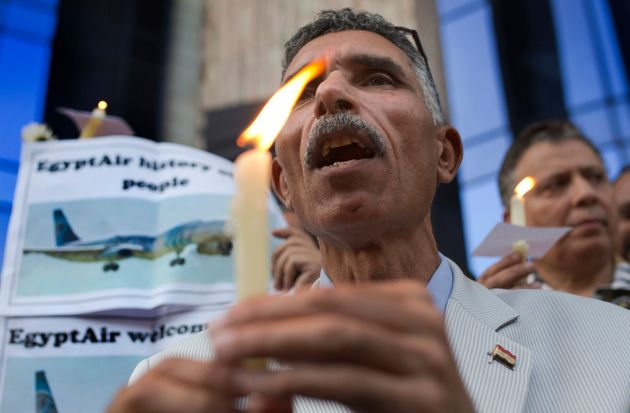 An Egyptian journalist holds a candle and a poster supporting EgyptAir during a candlelight vigil for...