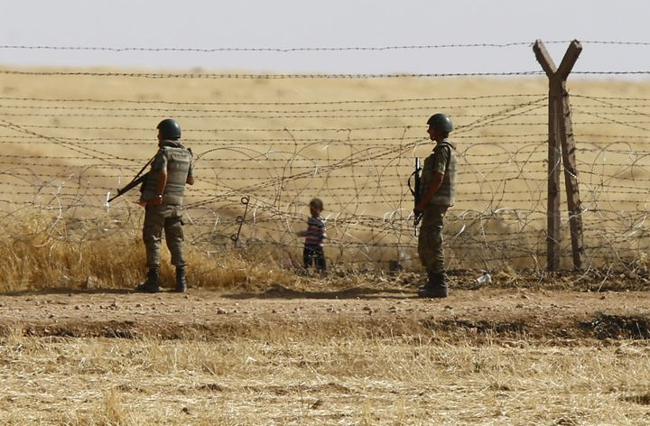 Turkish soldiers stand guard as a Syrian refugee boy waits behind the border fences to cross into Turkey on the Turkish-Syria