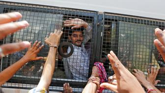 A man convicted in connection with a riot in Gujarat in 2002, waves from inside a police van outside of a court after a hearing in Ahmedabad, India June 9, 2016. REUTERS/Amit Dave TPX IMAGES OF THE DAY