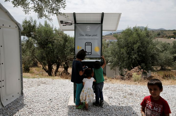 Children stand around a solar-powered charging station for mobile devices designed by a group of university students, at the