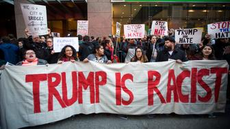 Protesters stand behind a banner reading 'Donald Trump is Racist' outside the New York State Republican Gala in New York, U.S., on Thursday, April 14, 2016. Despite Ted Cruz's rallying cry that his double-digit victory in Wisconsin last week would be a 'turning point' in the Republican presidential race, scant signs exist that the Texas conservative is gaining steam in critical upcoming contests in the Northeast, where billionaire Trump leads. Photographer: Michael Nagle/Bloomberg via Getty Images