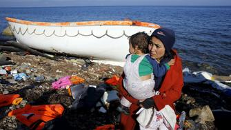 An Afghan migrant carries her baby after arriving by a raft on the Greek island of Lesbos November 19, 2015. Balkan countries have begun filtering the flow of migrants to Europe, granting passage to those fleeing conflict in the Middle East and Afghanistan but turning back others from Africa and Asia, the United Nations and Reuters witnesses said on Thursday. REUTERS/Yannis Behrakis      TPX IMAGES OF THE DAY