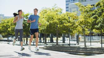 Couple jogging on urban sidewalk