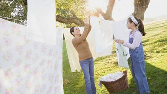 Hispanic mother and daughter hanging laundry on clothesline