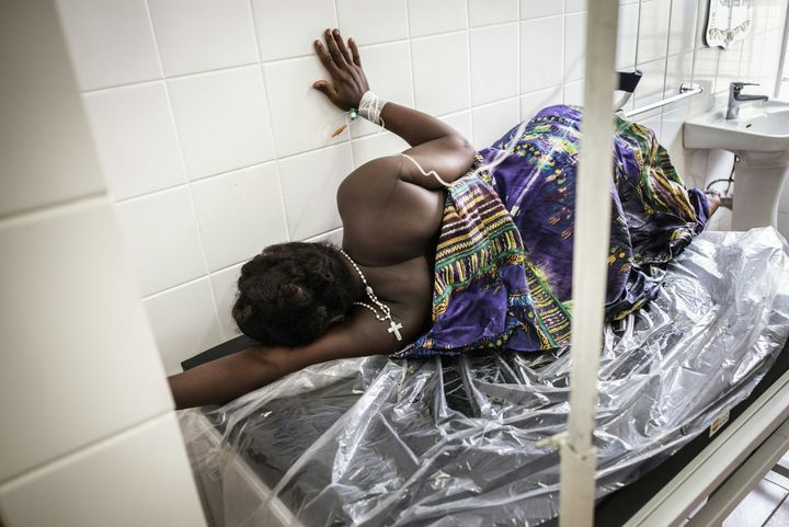 A pregnant woman in labour in pains uses the wall as a support at a ward of the Princess Christian Maternity Hospital in Free