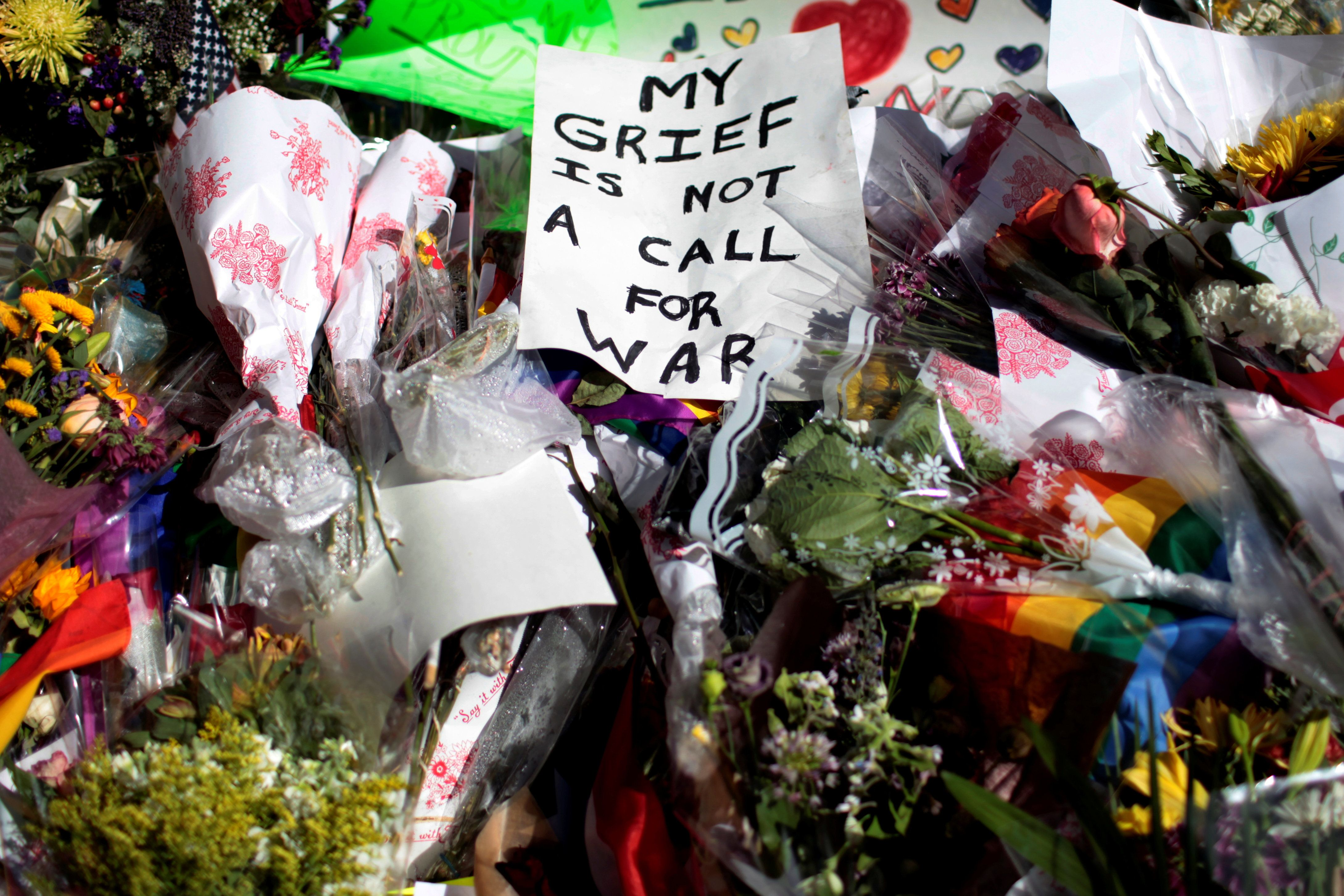 A sign sits atop a pile of flowers at a makeshift memorial to remember the victims of the mass shooting at a gay nightclub in Orlando, outside the Stonewall Inn in Manhattan, New York, U.S., June 15, 2016. REUTERS/Mike Segar