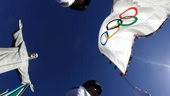 """Municipal Guards hold up the Olympic Flag in front of """"Christ the Redeemer"""" statue during a blessing ceremony in Rio de Janeiro August 19, 2012.  REUTERS/Ricardo Moraes (BRAZIL - Tags: SPORT OLYMPICS RELIGION)"""
