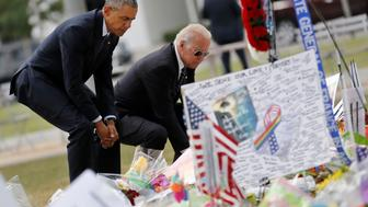 U.S. President Barack Obama (L) and Vice President Joe Biden pause as they place flowers at a makeshift memorial for shooting victims of the massacre at a gay nightclub in Orlando, Florida, U.S., June 16, 2016. REUTERS/Carlos Barria