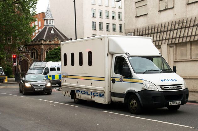 Two police cars and police vans arrive at Westminster Magistrates' Court ahead of Thomas Mair's