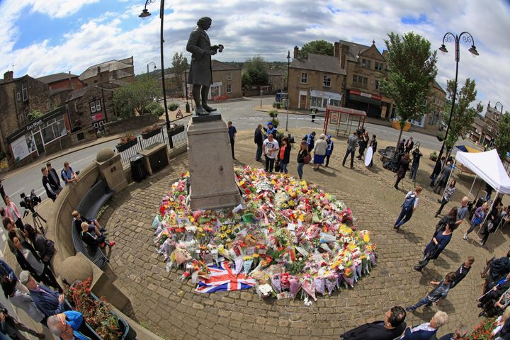 Locals view the growing amount of flowers and tributes to Jo Cox MP in Market Squre, Birstall, on Saturday.