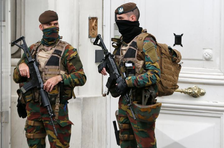 Belgian police arrested 12 suspects in a major anti-terror operation overnight. Above, Belgian soldiers stand guard outside t