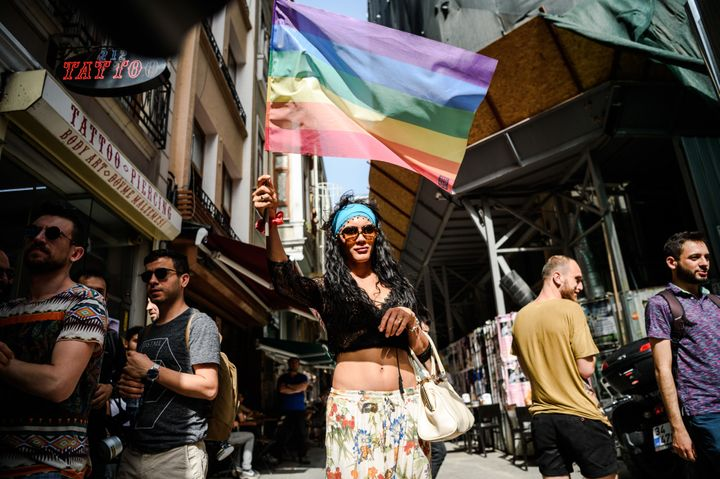 A woman holding rainbow flag look on as Turkish anti-riot police officers fire rubber bullets to disperse demonstrators.