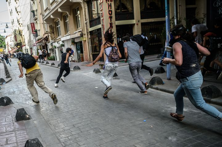 Demonstrators run as police forcibly disperse the rally.