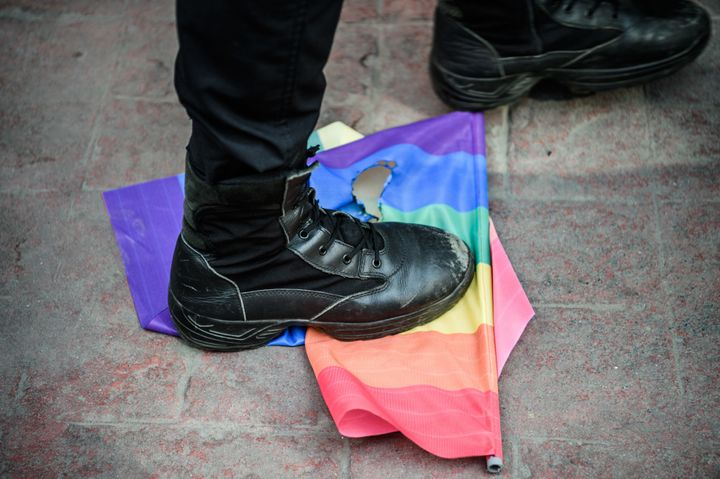 A Turkish anti-riot police officer steps on a rainbow flag during a rally staged by the LGBT community.