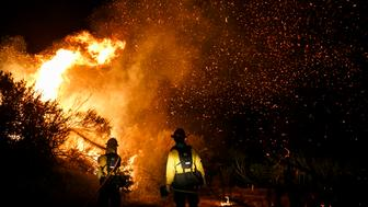 GOLETA, CA - JUNE 16: Firefighters try to control the blaze as they prevent the wildfire from burning through El Capitan Canyon camp and its structures,  on June 16, 2016 in Goleta, California. (Photo by Marcus Yam / Los Angeles Times via Getty Images)
