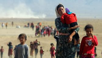 Displaced people from the minority Yazidi sect, fleeing violence from forces loyal to the Islamic State in Sinjar town, walk towards the Syrian border on the outskirts of Sinjar mountain near the Syrian border town of Elierbeh of Al-Hasakah Governorate in this August 11, 2014. REUTERS/Rodi Said/File Photo