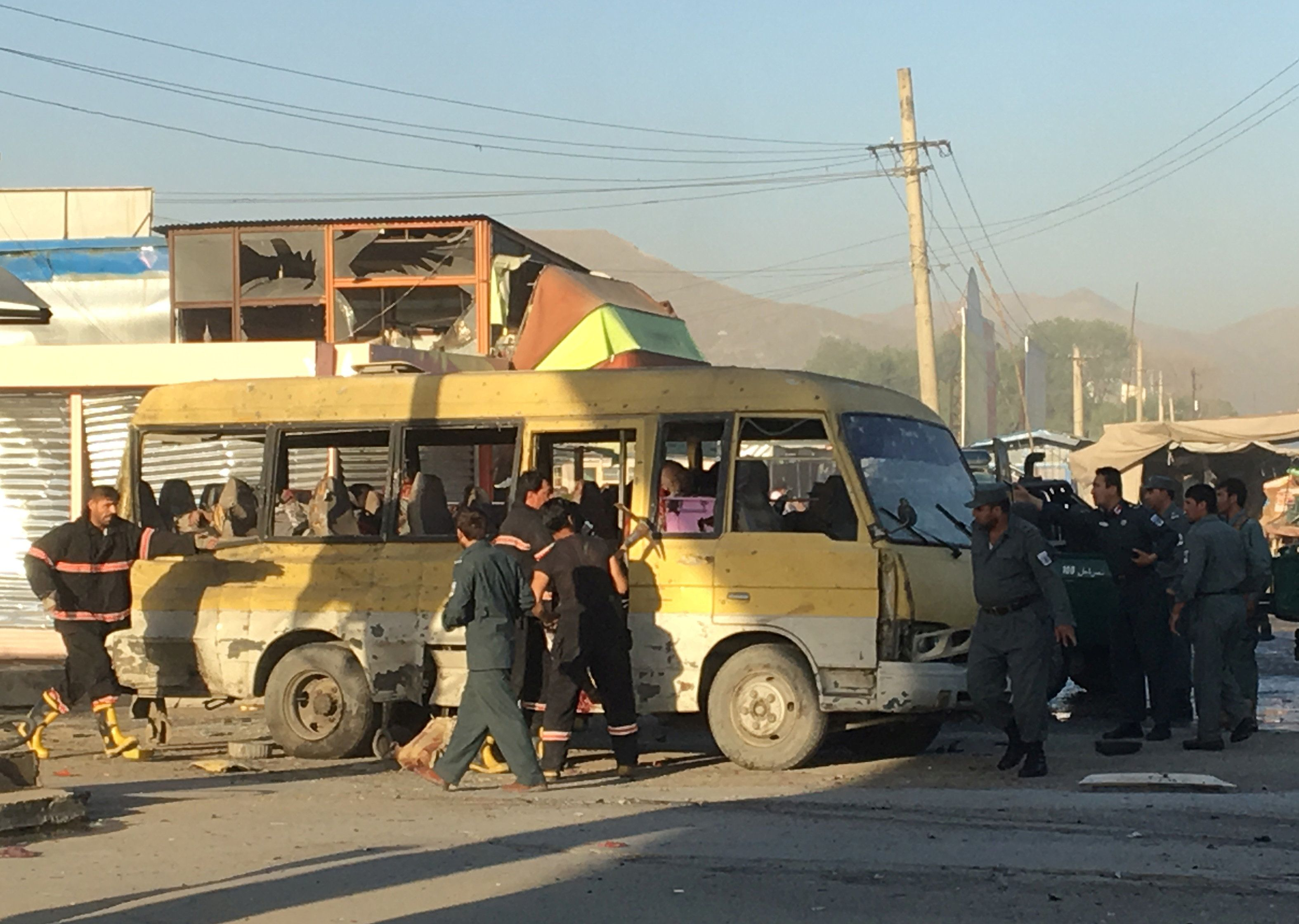 Police and fire fighters are seen at the site of a blast in Kabul on