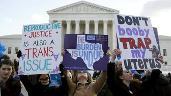 Protesters hold signs in front of the U.S. Supreme Court on the morning the court takes up a major abortion case focusing on whether a Texas law that imposes strict regulations on abortion doctors and clinic buildings interferes with the constitutional right of a woman to end her pregnancy, in Washington March 2, 2016. REUTERS/Kevin Lamarque