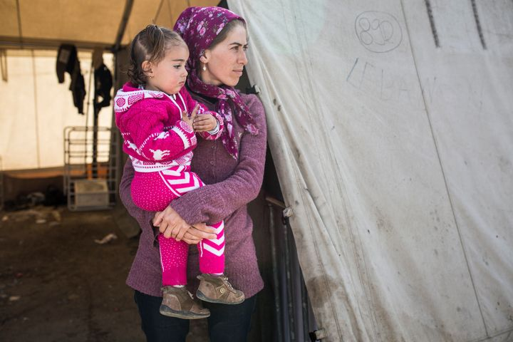 Makbola Kemal Ahmed, a Syrian Kurd from Afrin, stands outside the tent she lived in at Idomeni Camp with her 18-month-old dau