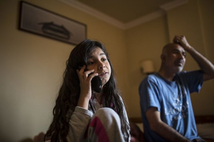 Zeyneb Omer, a 13-year-old Syrian girl from Aleppo, speaks with her mother over Skype, as her father sits nearby. She hasn't