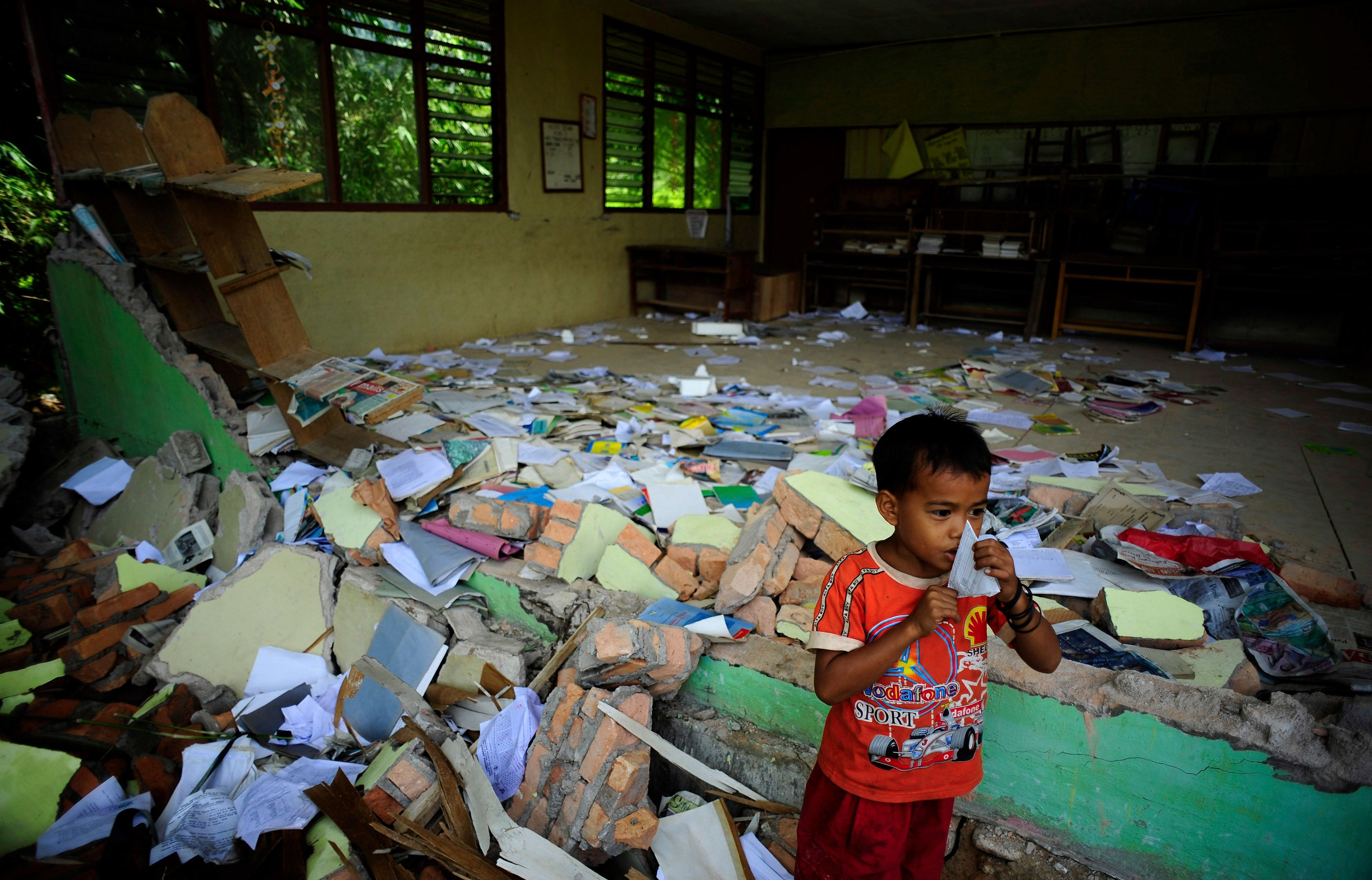 A boy plays outside his earthquake-destroyed classroom at the Timbalun Primary School Number 2 in a village on the outskirts of Padang, Indonesia's West Sumatra province, in the early hours of October 7, 2009.  REUTERS/Dylan Martinez     (INDONESIA ENVIRONMENT DISASTER EDUCATION IMAGES OF THE DAY)