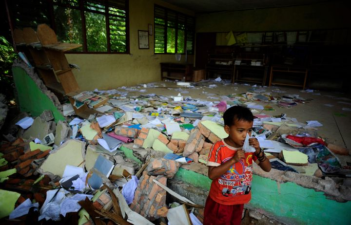 A boy stands outside his earthquake-destroyed classroom at the Timbalun Primary School Number 2 in a village on the outs