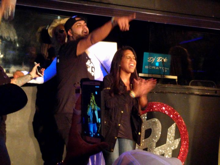 Two survivors of the shooting at Orlando's Pulse nightclub cheer as Puerto Rican merengue star Melina León performs on