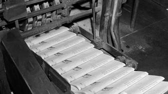 1960s CLOSE-UP OF PRINTING PRESS PUTTING OUT COMPLETED NEWSPAPERS  (Photo by H. Armstrong Roberts/ClassicStock/Getty Images)