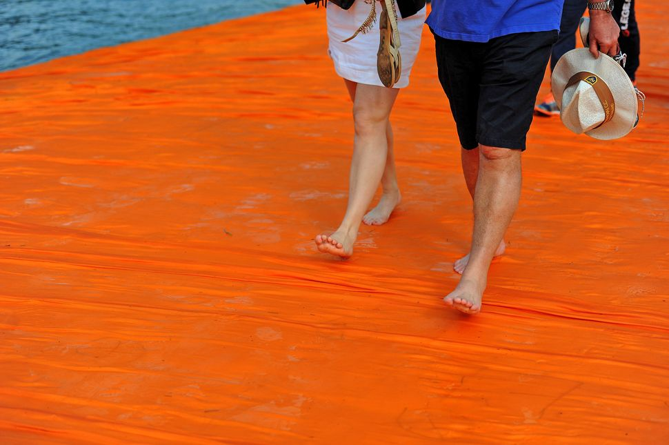 "People walk on the installation ""The Floating Piers"" on the Iseo Lake by the Bulgarian artist Christo Vladimirov Yavachev, kn"