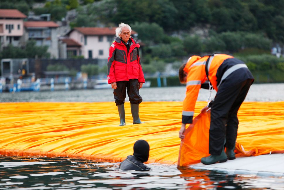 Christo is watching a diver hooking a fabric panel to the side of a floating pier on June 15, 2016.
