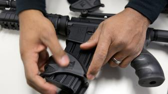 A New Haven police officer dismantles a Bushmaster semi-automatic assault rifle after it was turned in during a gun buyback event at the New Haven Police Academy in New Haven, Connecticut, December 22, 2012. The Bushmaster assault rifle seen is similar to the type used by 20-year-old Adam Lanza during the shooting at Sandy Hook Elementary school on December 14. The program, sponsored by the Injury Free Coalition for Kids of New Haven and Yale-New Haven Children's Hospital offered gift cards in exchange for working guns.  REUTERS/ Michelle McLoughlin (UNITED STATES - Tags: SOCIETY)